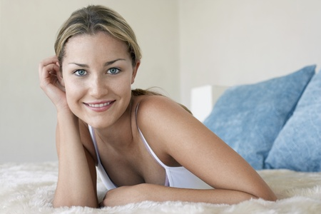 spaghetti strap: Young woman lying on bed portrait LANG_EVOIMAGES