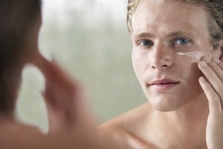 body concern: Man applying facial cream in front of mirror