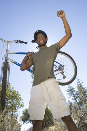 Man stands with arm raised holding a mountain bike Stock Photo - 12547739