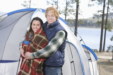 Man stands with arms around woman wrapped in blanket beside tent Stock Photo - 12547740