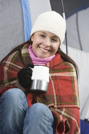 Woman sits in blanket holding cup outside tent Stock Photo - 12547741