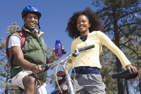 Young couple stand smiling with mountain bikes Stock Photo - 12547742
