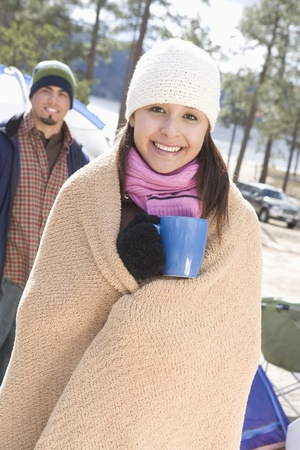 Woman stands in campsite wrapped in blanket and holding cup Stock Photo - 12547748