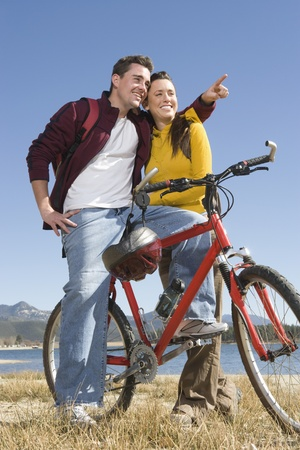 Young couple stand with mountain bike man pointing Stock Photo - 12547751