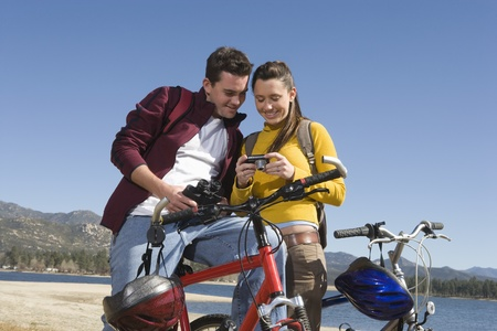 Young couple stand with mountain bike looking at screen of camera Stock Photo - 12547752