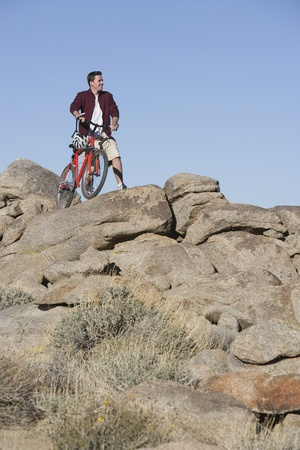 Man stands with mountain bike on rocky outcrop Stock Photo - 12547753