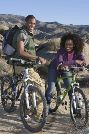 off road biking: Young couple stand smiling with mountain bikes