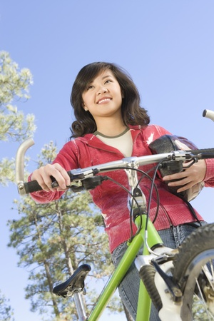 Young Asian woman stands with cycling helmet and mountain bike Stock Photo - 12547760