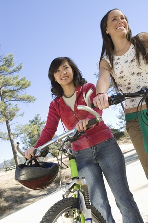 Two women stand with mountain bikes Stock Photo - 12547761