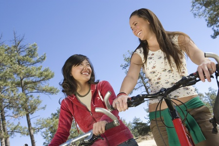 Two women stand smiling with mountain bikes Stock Photo - 12547762