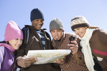 Group of friends stand looking at map together Stock Photo - 12547770