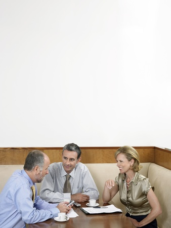 two people with others: Businesspeople having meeting in restaurant