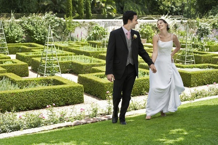 Bride and groom walking hand in hand in garden Stock Photo - 12547806