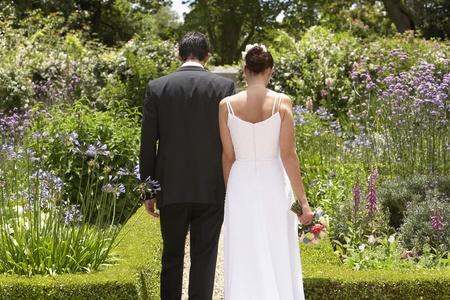 Bride and groom walking in garden back view Stock Photo - 12547807
