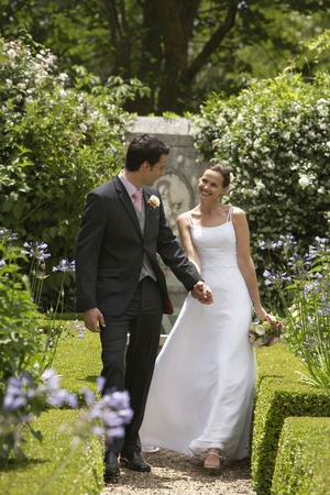Bride and groom walking in garden back view Stock Photo - 12547808