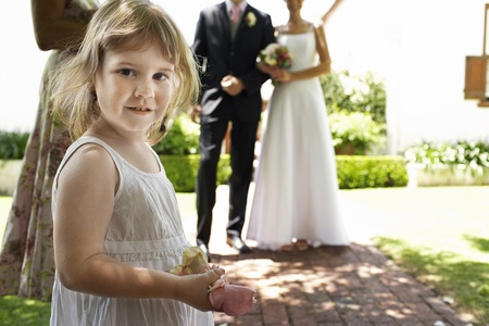 wedding guest: Young girl holding flower petals bride and groom standing in background
