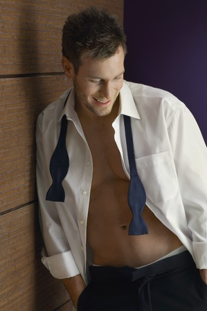 shirt unbuttoned: Man wearing tuxedo looking down indoors