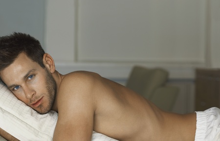 partially nude: Man lying down at home portrait