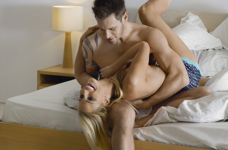 semi nude: Couple embracing on bed LANG_EVOIMAGES