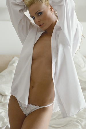 eroticism: Woman wearing shirt and underwear in bedroom portrait