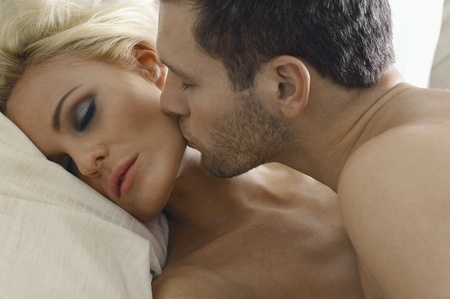 cropped: Man kissing woman asleep in bed close-up