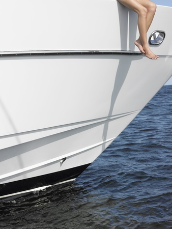 partially nude: Young woman sitting at edge of yacht with legs dangling overboard low section LANG_EVOIMAGES