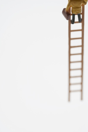 low section: Businessman figurine climbing ladder low section