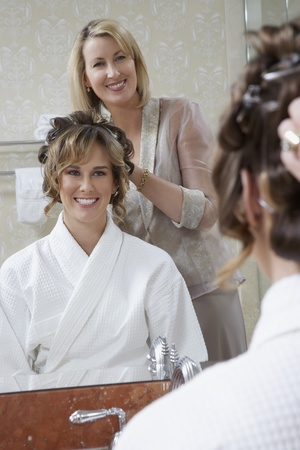 Mother dressing daughter's hair in mirror Stock Photo - 12547913
