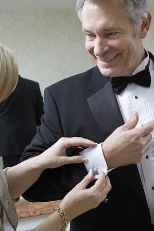 cufflink: Middle-aged woman fastening husbands cufflink