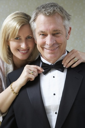 Middle-aged woman tying husband's bow tie portrait Stock Photo - 12547931