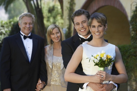 two people with others: Bride and groom with parents in background portrait