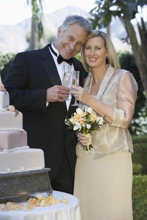 Middle-aged couple toasting near wedding cake portrait Stock Photo - 12547949
