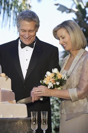 Middle-aged couple cutting wedding cake portrait Stock Photo - 12547950