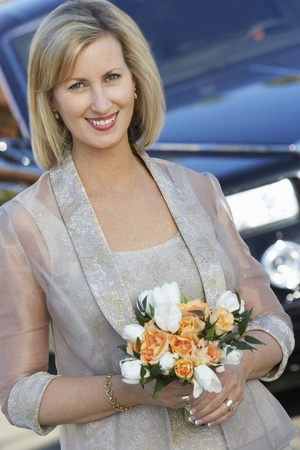 Middle-aged woman holding bouquet in front of limousine portrait Stock Photo - 12547969