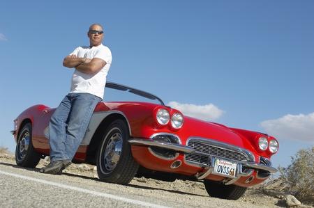 coche clásico: El hombre de pie al lado de autos cl�sicos en la carretera