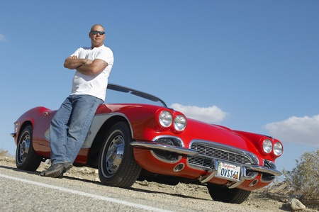 classic car: Man standing beside classic car on road LANG_EVOIMAGES