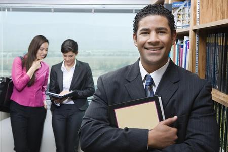 Business man standing near bookshelf in library portrait Stock Photo - 12548007