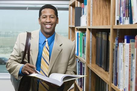 Business man standing by bookshelf portrait