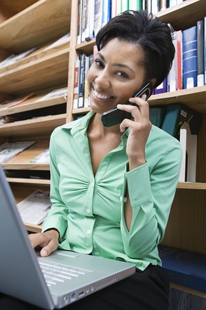 Woman using laptop and mobile phone in library Stock Photo - 12548009