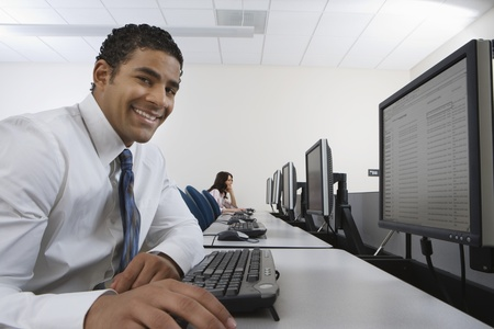 Man sitting at desk in front of computer Stock Photo - 12548019