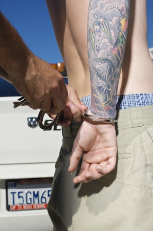 being arrested: Officer Handcuffing Tattooed Young Man