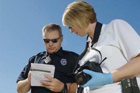 investigaci�n: El oficial de polic�a e investigador con la c�mara LANG_EVOIMAGES