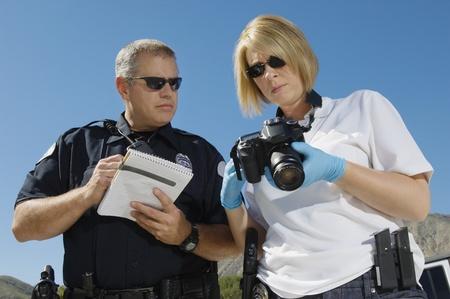 El oficial de policía e investigador con la cámara Foto de archivo