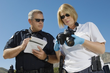 enforcing the law: Police Officer and Investigator with Camera