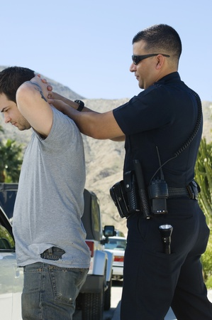 Police Officer Arresting Young Man Stock Photo - 12548051