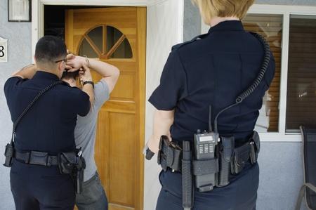 arrest women: Police Officer Arresting Young Man LANG_EVOIMAGES