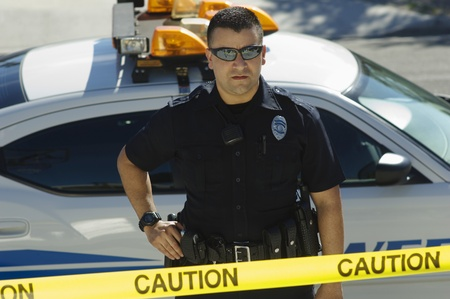 Police Officer Standing Behind Police Tape Stock Photo - 12548054