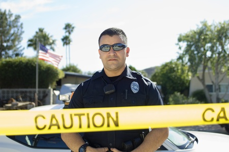 Police Officer Standing Behind Police Tape Stock Photo - 12548055