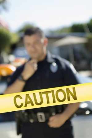 Police Officer Standing Behind Police Tape Stock Photo - 12548056