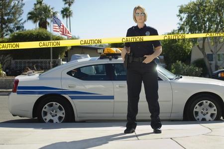enforcing: Police Officer Standing Behind Police Tape LANG_EVOIMAGES